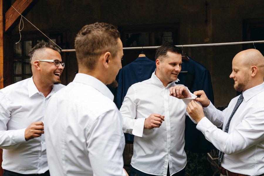 drużbowie i przyjacie pomagają panu młodemu zapiąć spinki przy koszuli, fotografia ślubna Dobczyce