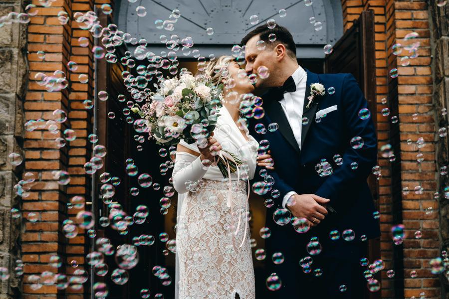 dwór kociołek wesele, para młoda wychodzi z kościoła, bańki mydlane zamiast konfetti
