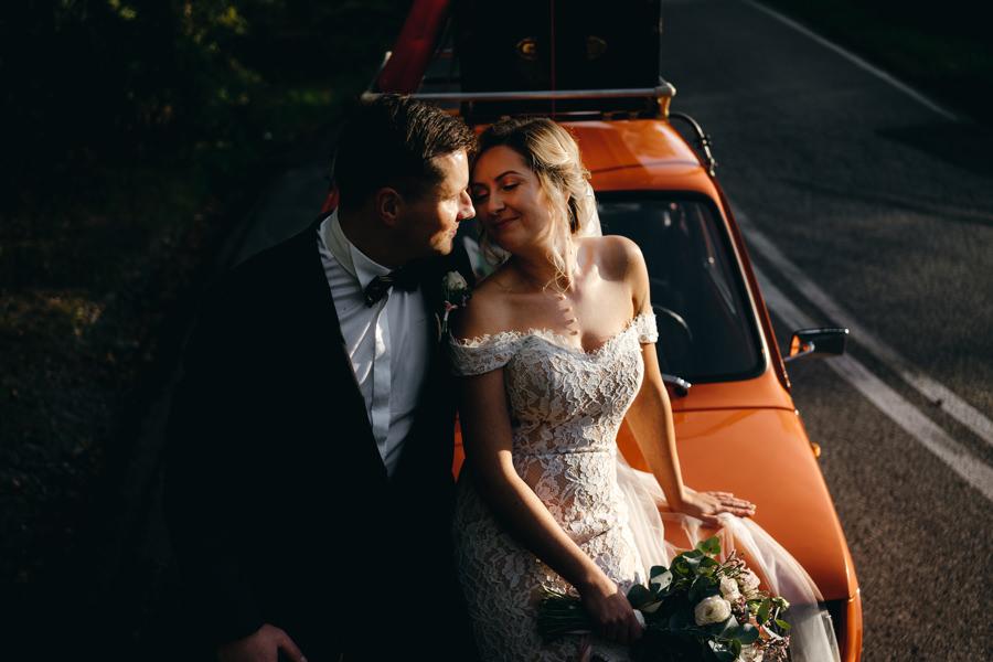 fiat 126p, zachód słońća, fotografia ślubna, portret pary młodej, dwór kociołek wesele złota godzina, sesja w dniu ślubu