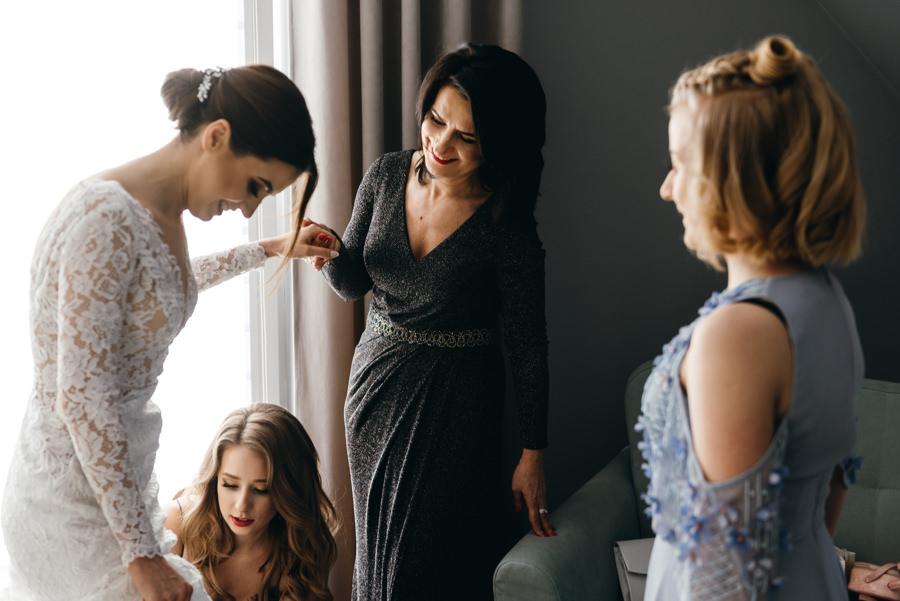 panna młoda przygotowuje się do ślubu, fotografia ślubna Bochnia, mama pomaga ubrać suknie pannie młodej