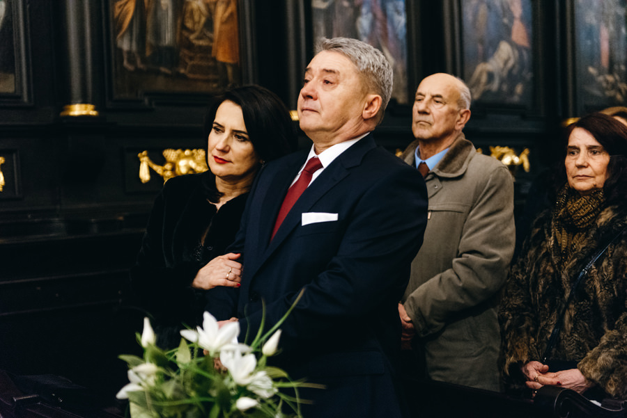 wzruszeni rodzice patrzą na przysięgę ślubną pary młodej