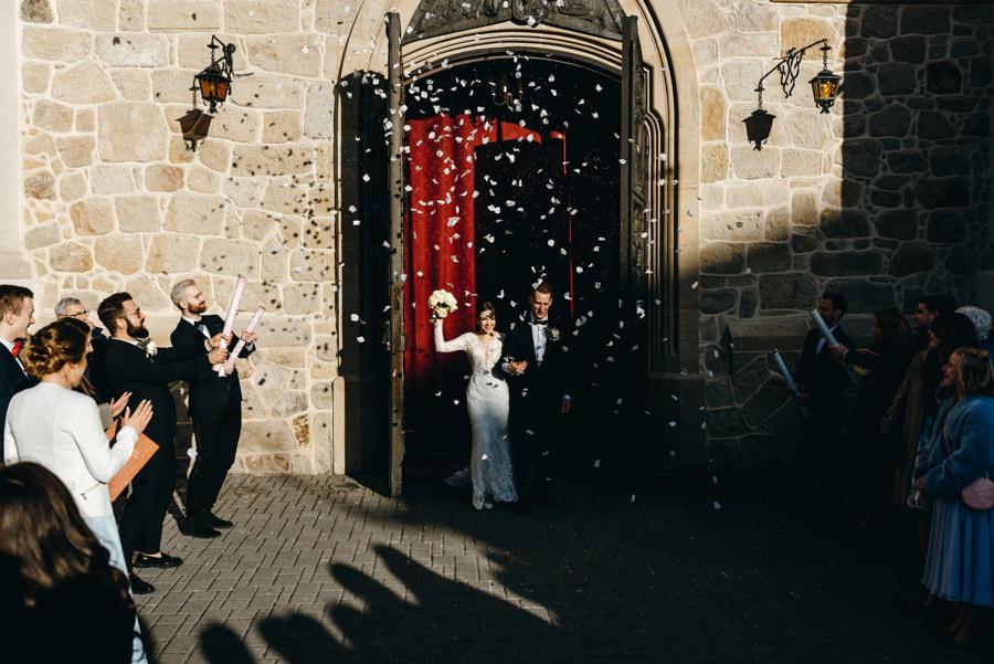 para młoda wychodzi z Bazyliki św. Mikołaja w Bochni po ceremonii ślubnej