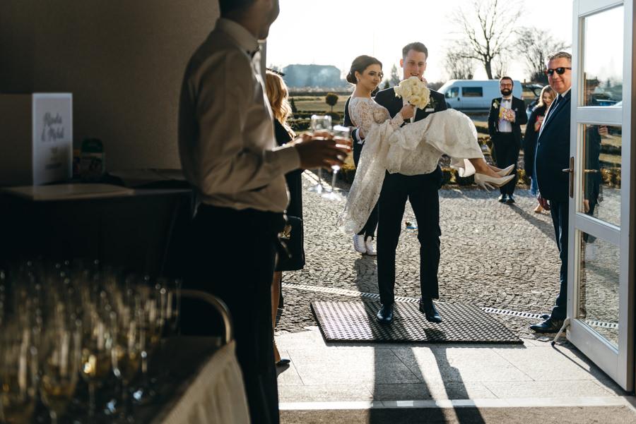 pan młody przenosi żonę przez próg, Hotel Panorama Garden, wesele, reportaż ślubny, Fotograf Bochnia