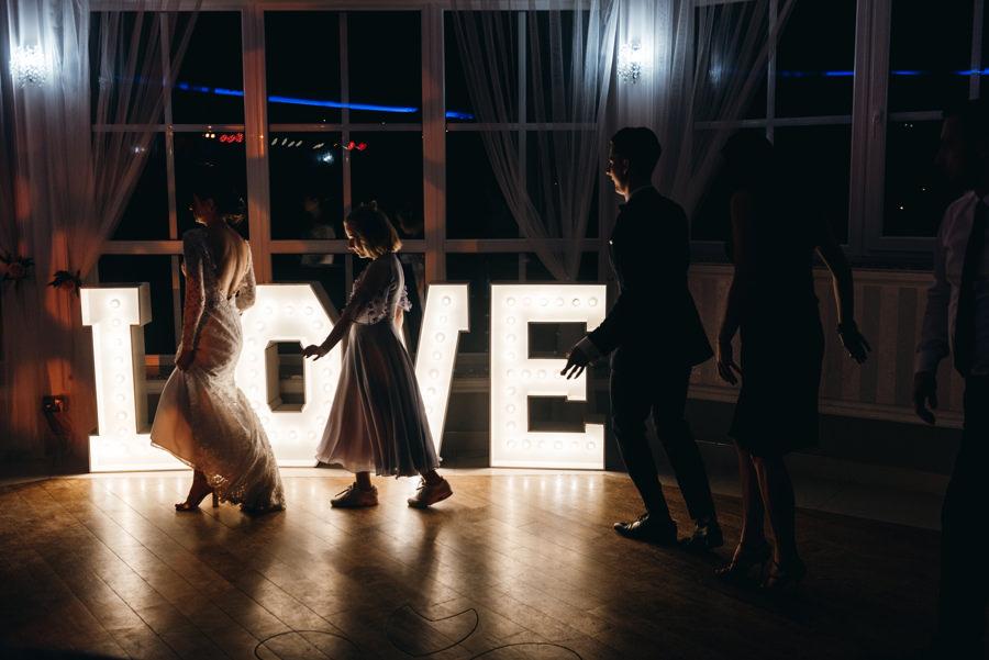 napis love ze światełek, sylwetki tańczących ludzi, hotel panorama garden wesele